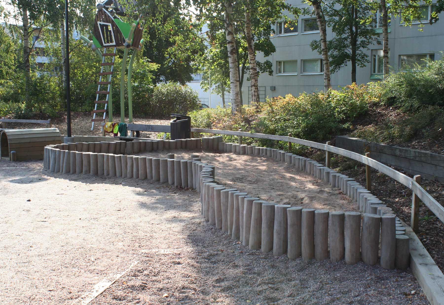 Robia-pölkyt rajaavat lasten hiekkalaatikkoa
